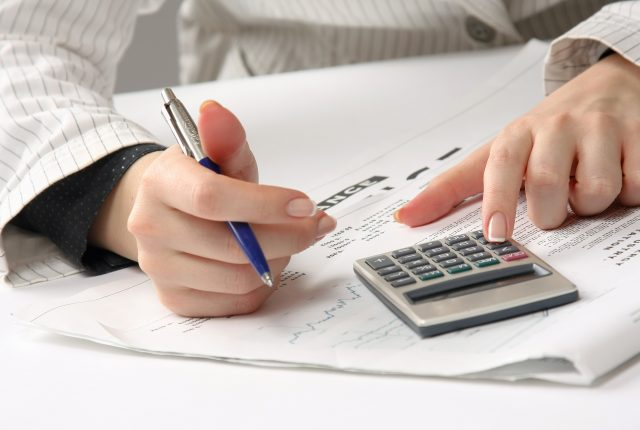 business woman review tax documents with calculator