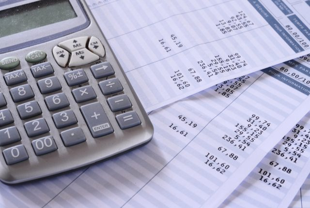 salary and payroll data sitting beneath a calculator